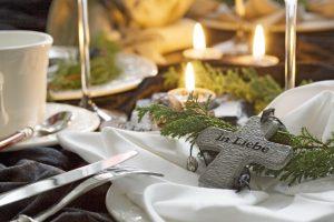 Festliches Gedeck an der Leichenschmaus Tafel mit brennenden Kerzen und einem Holzkreuz. Leichenschmaus Lokale Wien.