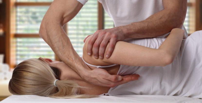 Männlicher Osteopath mit schönen starken Armen, der die Schultern und den Nacken einer jungen blonden Patientin (Rückenansicht) behandelt. Osteopathie Graz.