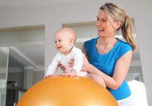 Junge blonde Osteopathin, die mit einem Baby arbeitet. Osteopathie Linz.