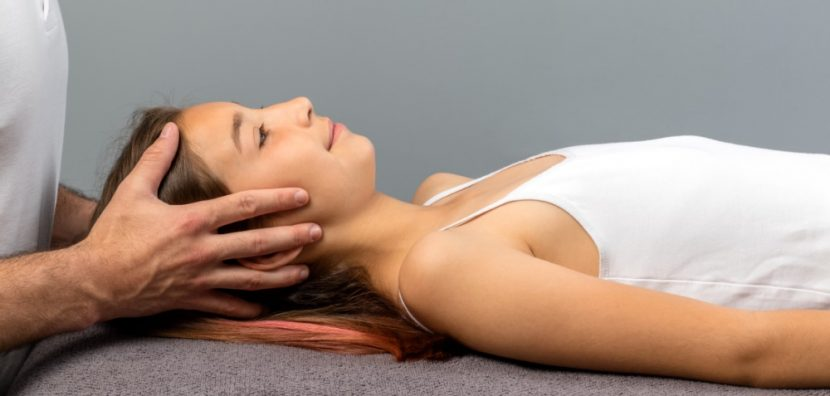 Junge Frau mit dunklen Haaren und weißem Top, die auf einer Behandlungsliege am Rücken liegt und osteopathisch behandelt wird. Osteopathie Linz.