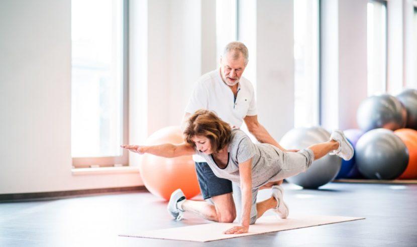 Älterer Physiotherapeut in weißem T-Shirt, der mit einer Patientin Rückenschule macht. Physiotherapie Linz.