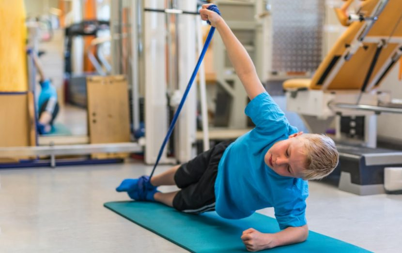 Blonder Junge, der mit Physiotape auf einer Gymnastikmatte trainiert. Physiotherapie Linz.