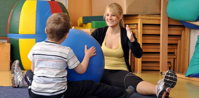Blonde Physiotherapeutin bei der Behandlung eines kleinen Jungen. Physiotherapie Wien.