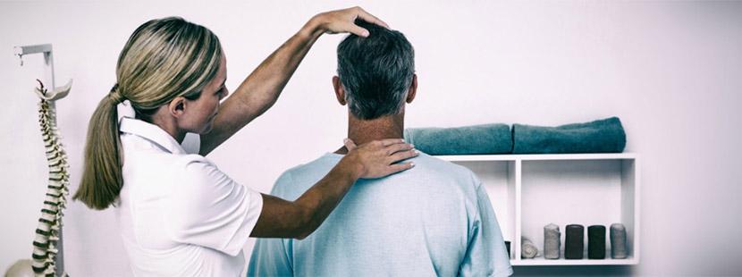 Blonde Physiotherapeutin, die den Nacken eines Patienten behandelt. Physiotherapie Wien.