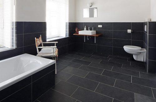 Ein Badezimmer mit moderner Einrichtung und schwarzen Schieferfliesen als Bodenbelag und Wandverkleidung.
