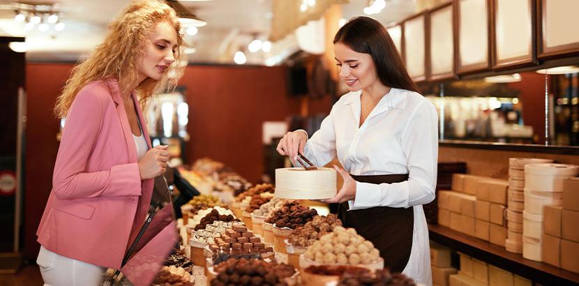 Hübsche brünette Verkäuferin einer Schokothek Wien, die einer blonden Kundin eine Geschenkschachtel mit Pralinen füllt.