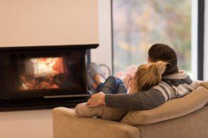 Junges Paar sitzt vor einem geschlossenen Gaskamin mit Sichtfenster und Scheitholzimitaten aus feuerfester Keramik.