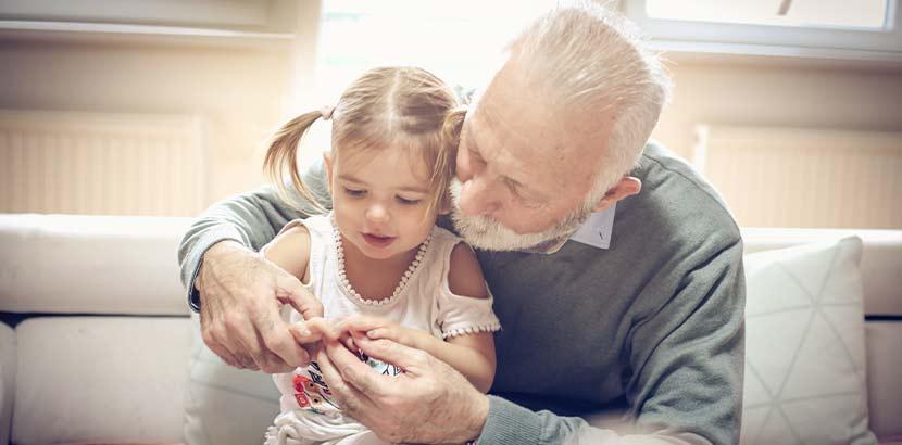 Großvater, der mit seiner kleinen Enkelin spielt. Bestattungskosten, Begräbniskosten.