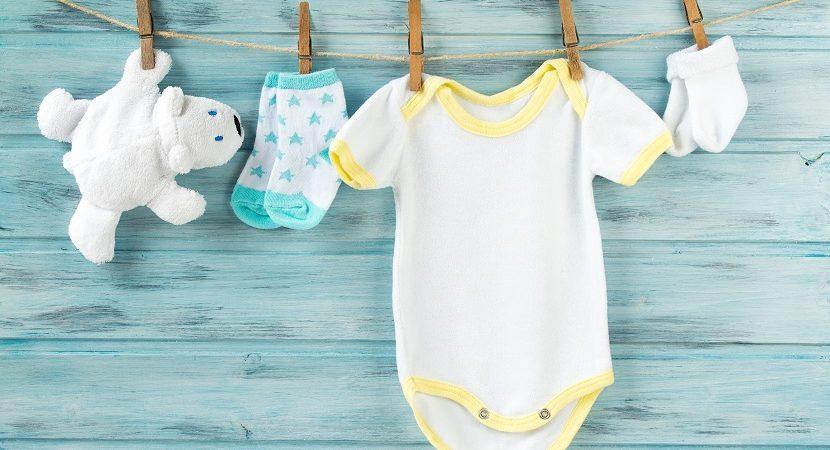 Babykleidung an einer Wäscheleine mit Kluppen aufgehängt