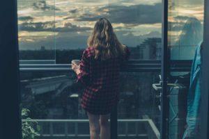 Frau steht vor verglastem Balkon und sieht in die Ferne