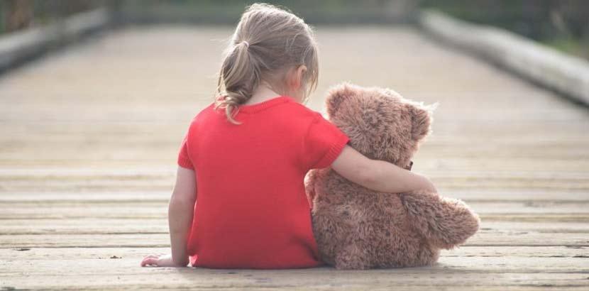 Kleines Mädchen im roten T-Shirt, das mit dem Rücken zur Kamera auf einem Steg sitzt und ihren Teddybären im Arm hält. Bestattungskosten Wien.