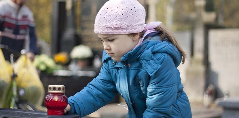 Kleines Mädchen in türkiser Jacke, die am Friedhof ein Grablicht auf eine Grabplatte stellt. Bestattungskosten Wien.