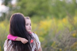 Kleines Mädchen, das von ihrer Mutter im Arm gehalten wird. Bestattungskosten, Begräbniskosten.