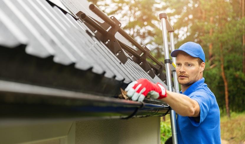 Mann reinigt Dachrinne auf Leiter