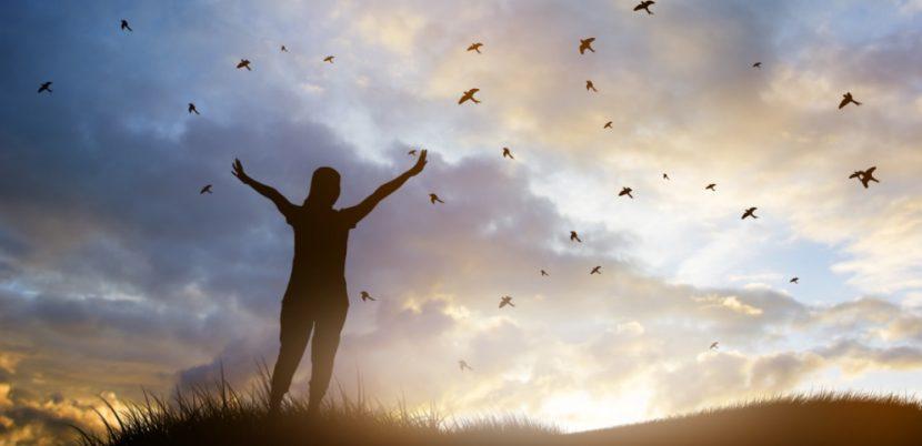 Junge Frau, die im Morgengrauen im Freien steht und eine Siegerpose einnimmt. Am Himmel fliegen Vögel. Familienaufstellung Wien, Graz, Linz.