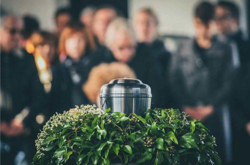 Trauerfeier mit silberner Urne im Vordergrund und Trauergästen im Hintergrund. Feuerbestattung Wien.