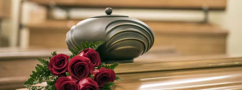 Dunkle, sparsam verzierte Urne während der Trauerfeier auf einem hellen Nussholzsarg neben roten Rosen. Feuerbestattung Wien Kosten.