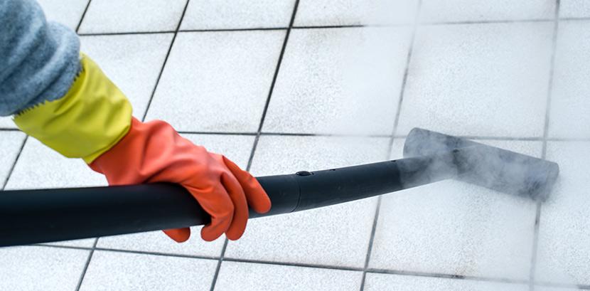 Eine Person reinigt mit einem Dampfreiniger schwarze Fugen.