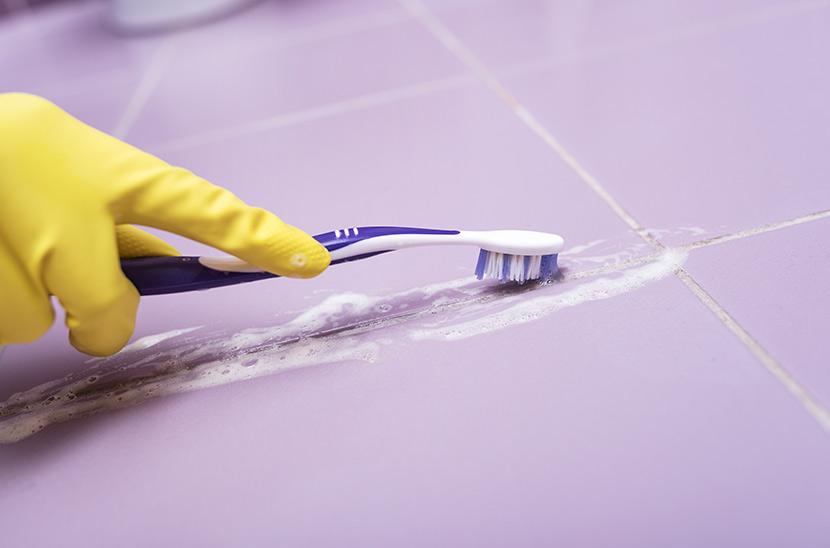Eine Hand in einem gelben Gummihandschuh schrubbt mit einer Zahnbürste Fugen zwischen lila Fliesen.