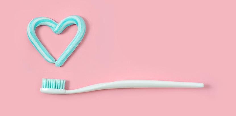 Eine Zahnbürste und ein Herz aus Zahnpasta auf einem Rosa Untergrund.