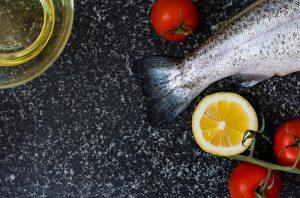 Eine dunkle Platte aus Granit, auf der eine Schale Öl, ein roher Fisch, Tomaten und eine aufgeschnittene Zitrone liegen.