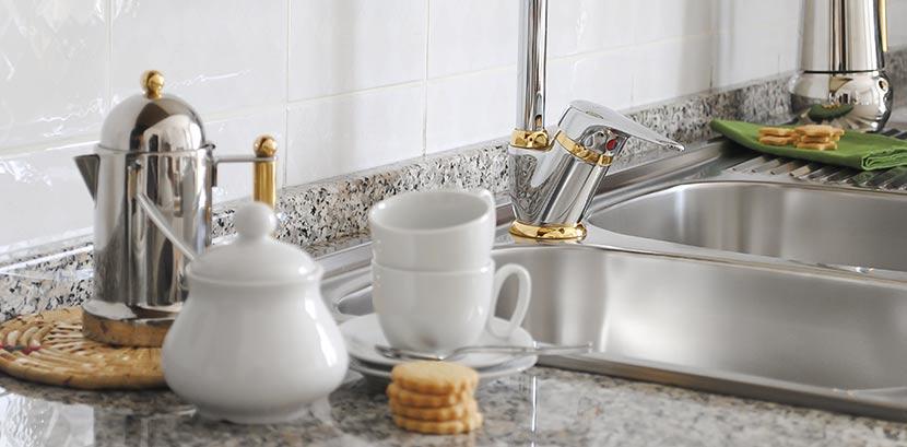 eine k che mit einer arbeitsplatte aus granit neben der abwasch. Black Bedroom Furniture Sets. Home Design Ideas