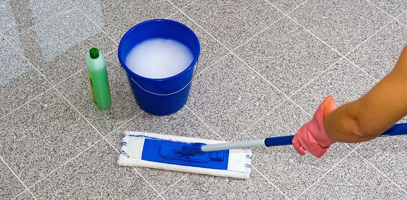 Eine Frau reinigt Granitfliesen mit Wasser, einem Mopp und Reinigungsmittel.