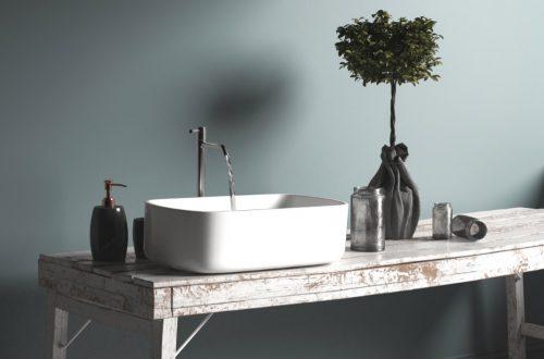Vintage Waschtisch vor blauer Wand mit laufendem Wasserhahn, der sein Wasser über ein Hauswasserwerk aus einer Zisterne bezieht.
