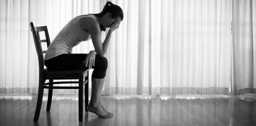 Junge Frau mit hochfunktionaler Depression, die auf einem Stuhl sitzt und den Kopf mit ihren Händen stützt.