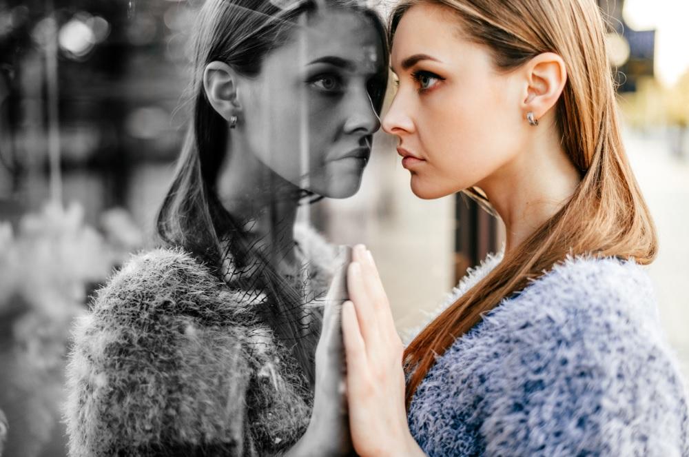 Junge Frau mit high functioning depression, die versucht, ihr Gesicht zu wahren.
