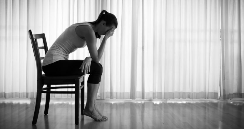 Junge Frau, die im abgedunkelten Raum auf einem Stuhl sitzt und den Kopf in die Hände stützt. High Functioning Depression.