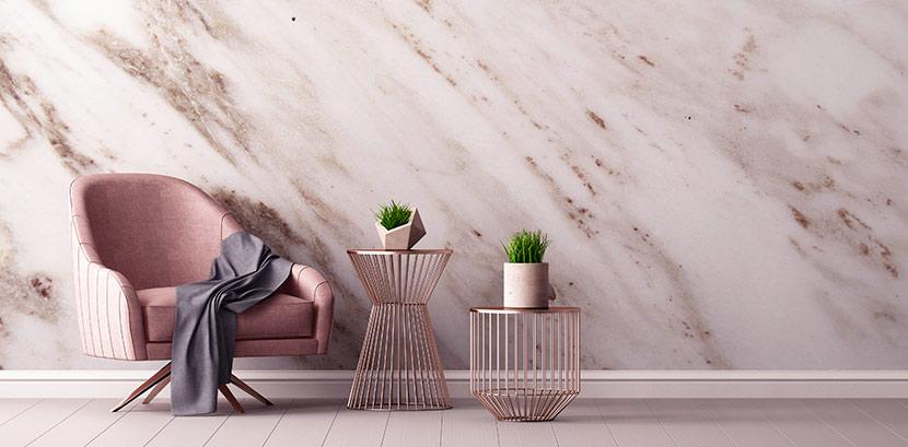 Ein Raum mit einer hellen Marmorwand. Darin steht ein Sofasessel in Altrosa mit Holzbeinen. Auf dem Sessel liegt eine blaue Decke, daneben stehen zwei moderne Beistelltische aus Draht in Roségold. Darauf stehen zwei Sukkulenten in modernen, hellen Töpfen.