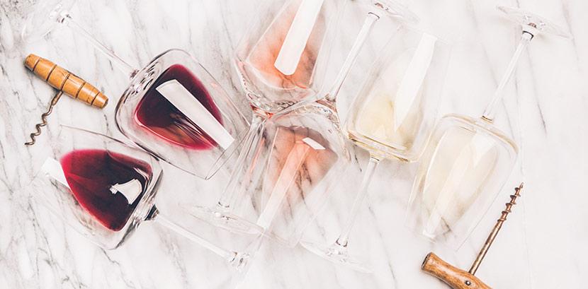 Gläser mit Rotwein, Rosé Wein und Weißwein auf einer Marmor Oberfläche. Daneben liegen Korkenzieher.