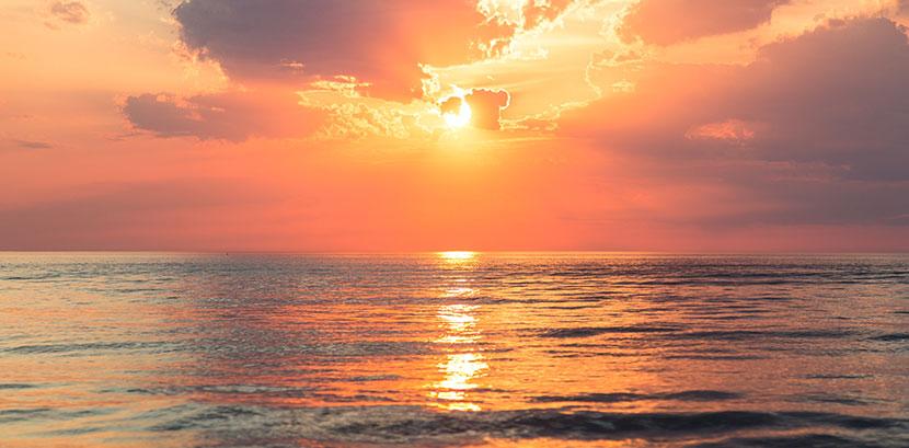 Sonnenallergie: Die Sonne geht über dem Meer unter.