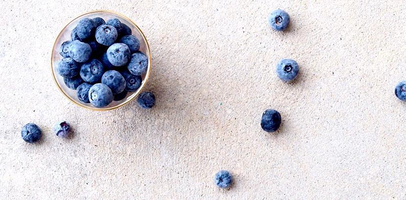 Blaubeeren / Heidelbeeren in einem Schälchen auf einem Tisch: Sie sollen durch ihre Anitoxidantien Sonnenallergie vorbeugen.