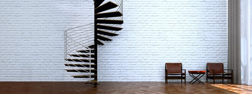 Wendeltreppe mit Säule: Eine Spindeltreppe führt in einen Raum mit Parkettboden und weißer Ziegelmauer. Im Raum stehen zwei Ledersessel und ein kleiner Klapptisch.