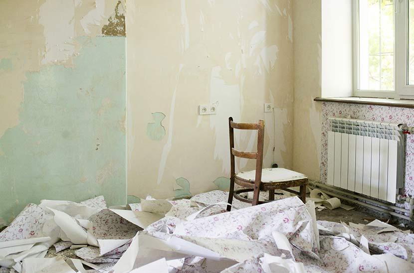 Tapete entfernen: Ein Raum, in dem eine große Menge alte Tapete auf dem Boden liegt und ein Stuhl steht.