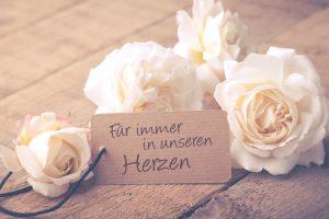 Vier weiße Rosen verteilt um einen Schild, das sich auf einen Todesfall bezieht. Todesfall Checkliste Österreich.