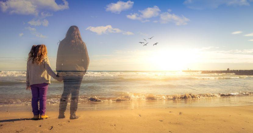 Mädchen am Strand bei Sonnenuntergang, hält die Hand ihrer verstorbenen Mutter, die ihr als Geist erscheint. Trauer Therapie Wien.