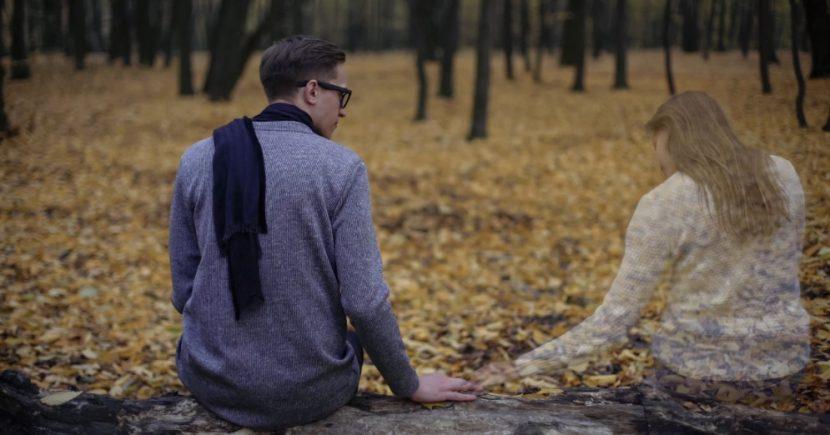 Junger Mann in Trauer, der auf einer Waldlichtung seiner verstorbenen Frau gedenkt. Trauerbewältigung und Trauerhilfe Wien.