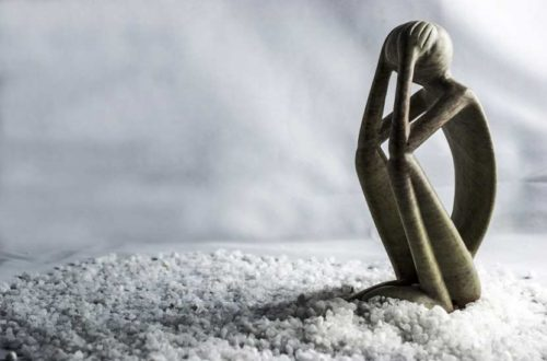 Holzfigur vor weißem Hintergrund in trauriger, trauernder Pose. Trauerbegleitung und Trauerhilfe Wien.