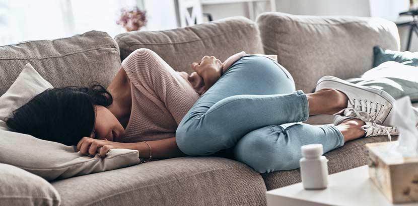 Junge dunkelhaarige Frau, die weinend auf dem Sofa liegt. Trauerbegleitung Wien.