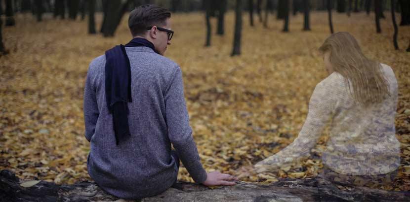 Junger Mann in Trauer, der auf einer Waldlichtung seiner verstorbenen Frau gedenkt. Trauerbegleitung Wien.