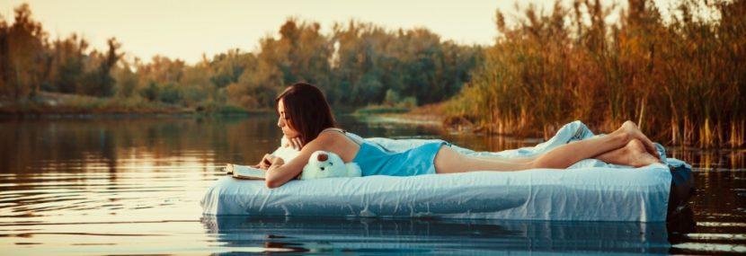 Schöne junge Frau, die auf einem Wasserbett im See liegt und liest. Wasserbetten Wien Preise.