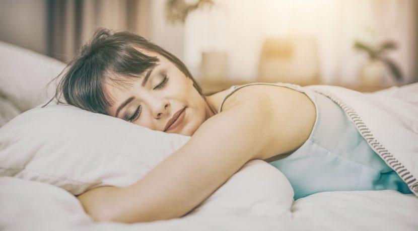 Hübsche junge Frau mit dunklen Haaren, die in den frühen Morgenstunden in ihrem Bett schläft. Wasserbetten Preise Wien.