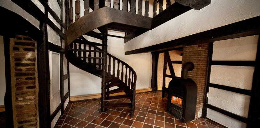 Wendeltreppe im Landhausstil aus dunklem Massivholz in einem Haus