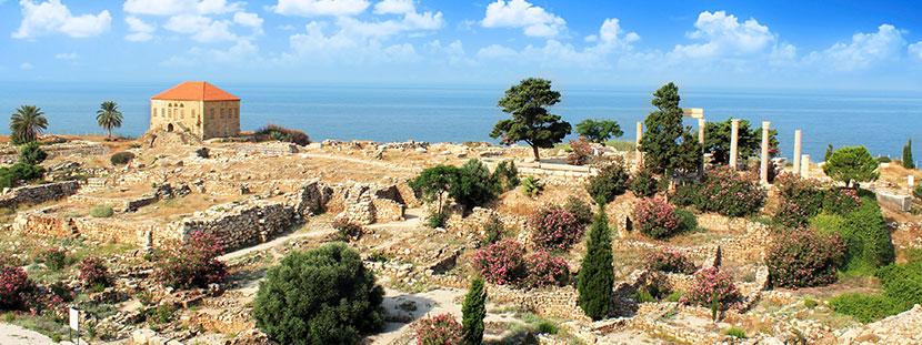 Eine Landschaft an der Küste im Libanon mit einem kleinen Haus, Palmen und Zedern.