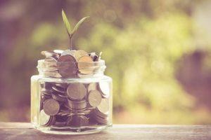 Glas, das mit Geld gefüllt ist, aus dem ein zartes Pflänzchen wächst. Steht sinnbildlich für die Geldersparnis durch eine Zisterne im Garten.