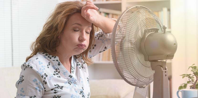 Frau mittleren Alters, die stark schwitzt und direkt vor dem Ventilator sitzt.