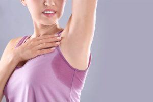 Junge Frau im rosa Top, auf dem sich ein sehr großer Schweißfleck unter dem Arm abzeichnet. Schweißdrüsen entfernen Wien.